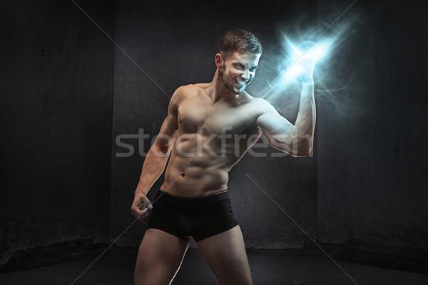 Muscular guy squeezing the power Stock photo © konradbak