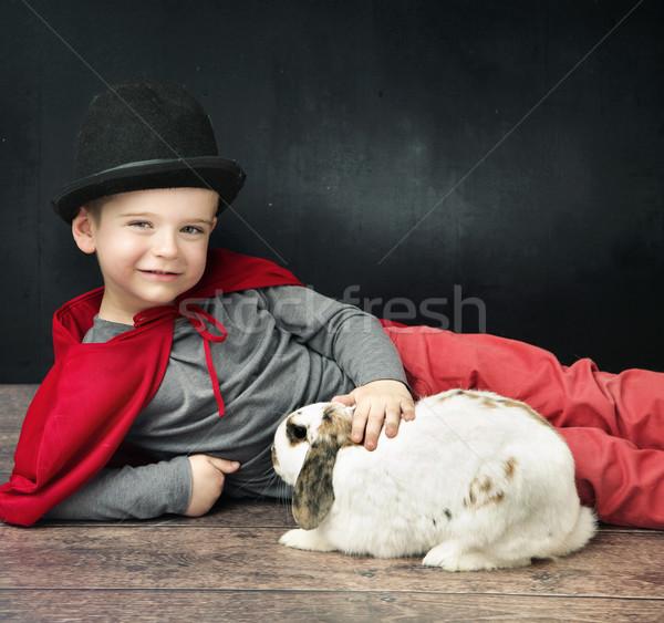 Little magician boy stroking a bunny Stock photo © konradbak