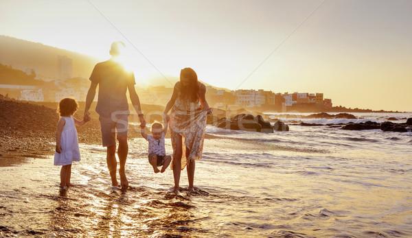 Cheerful family having fun on a beach, summer portrait Stock photo © konradbak