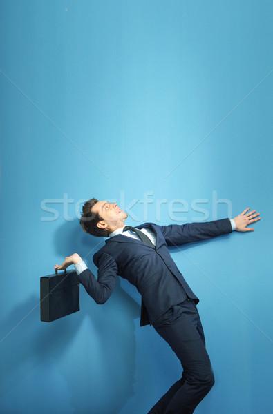 Elegant banker trying to throw out the suitcase Stock photo © konradbak