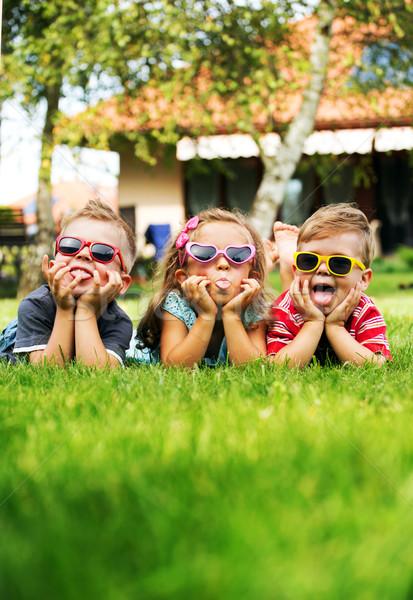 Trio kids showing their tongues Stock photo © konradbak