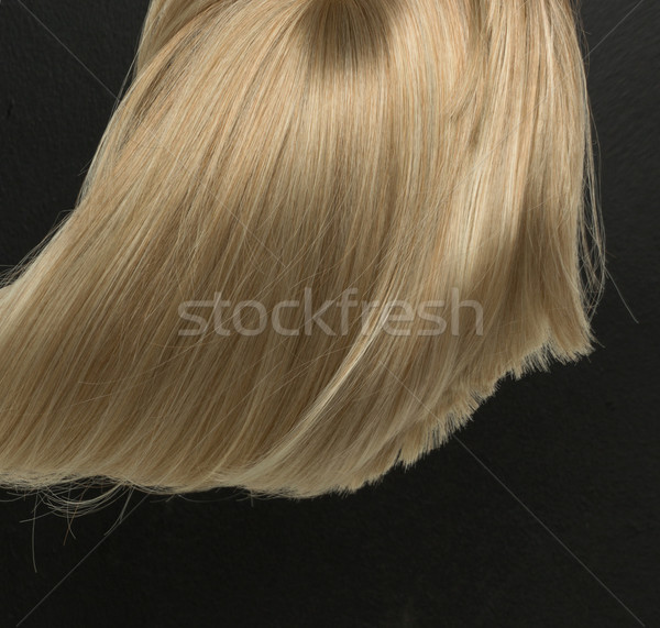 Dense, straight blond wig lying on black background Stock photo © konradbak