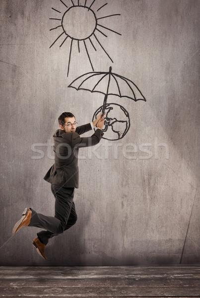 Man saving earth from global warming  Stock photo © konradbak