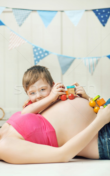 Cute boy playing with the unborn sibling Stock photo © konradbak