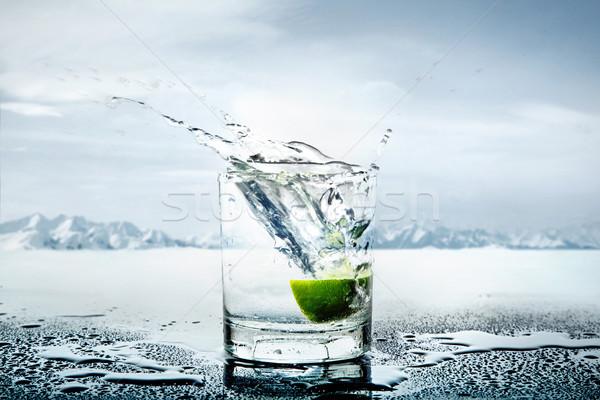 Art picture of lemon thrown to the glass of water Stock photo © konradbak