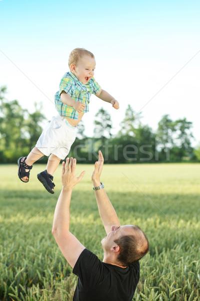 Caring father tossing his son Stock photo © konradbak