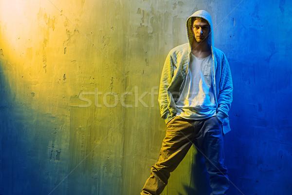 Handsome hi hop dancer leaning on  a concrete wall Stock photo © konradbak
