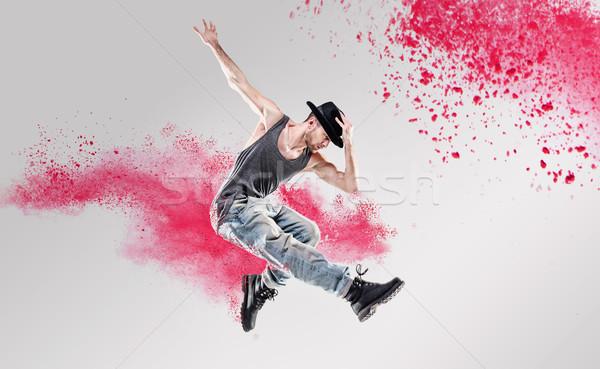 Portrait of a dancer excercising among a colorful dust Stock photo © konradbak