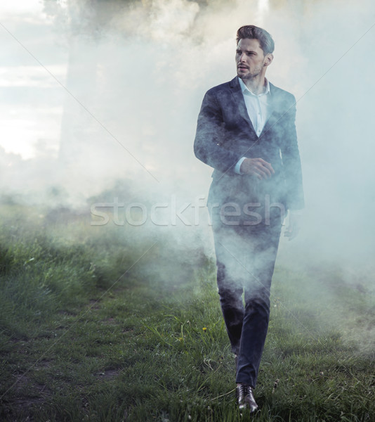 elegant young man walking in the morning haze Stock photo © konradbak