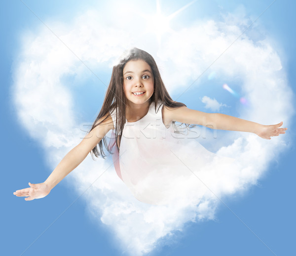 Stock photo: Little girl flying through a heartshaped cloud