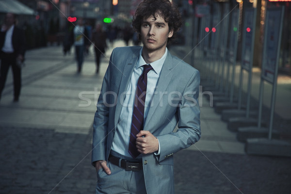 Handsome guy walking on a evening city street Stock photo © konradbak