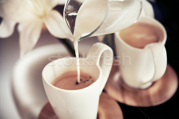 Two cups of coffee with decoration and poured milk Stock photo © konradbak
