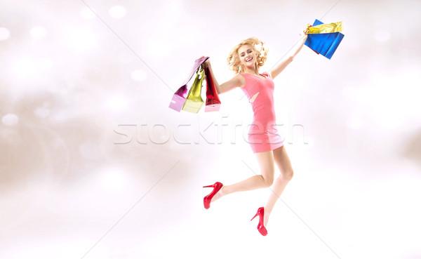 Delighted jumping lady with shopping bags Stock photo © konradbak