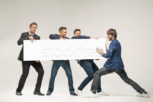 Group of handsome men pushing board Stock photo © konradbak
