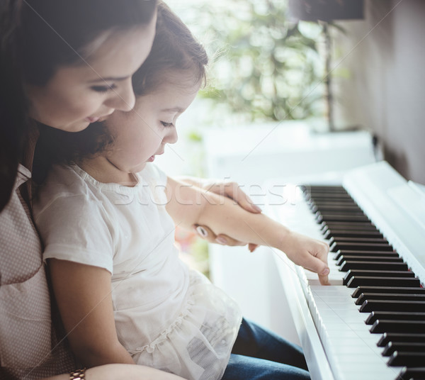 Mom teaching her daughter piano playing Stock photo © konradbak