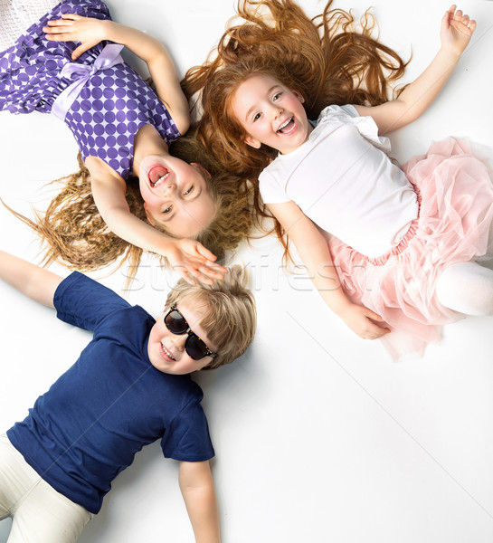 Portrait of siblings lying on a white background  Stock photo © konradbak