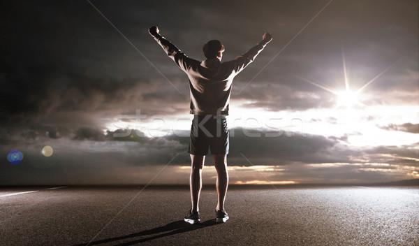 Portrait of an athlete looking at the dark clouds Stock photo © konradbak