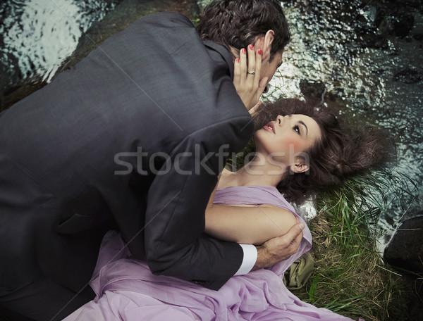 Loving couple laying on the grass Stock photo © konradbak