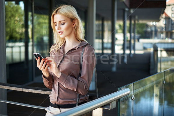Blond lady using her smartphone Stock photo © konradbak