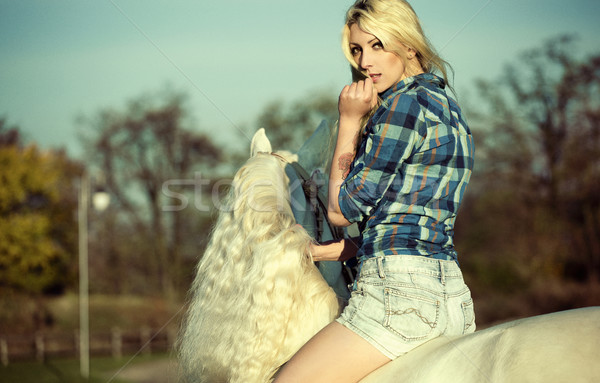 Mystery blonde woman riding a horse Stock photo © konradbak