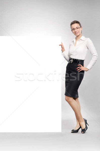 Attractive businesswoman showing empty white board Stock photo © konradbak