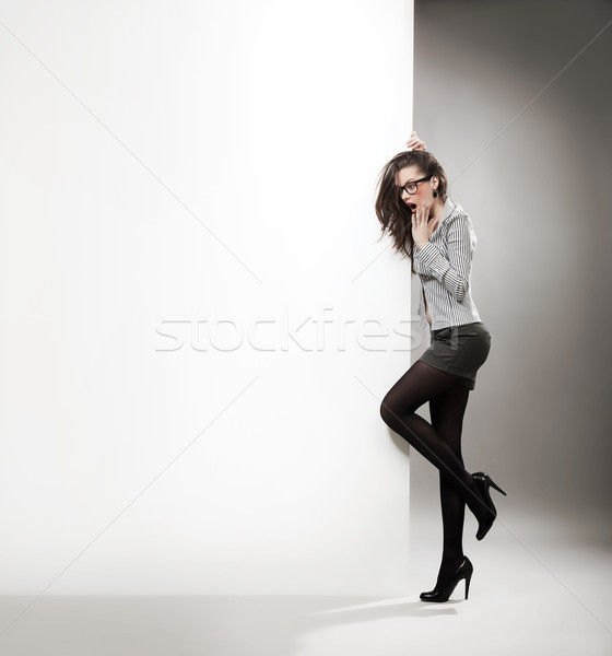 Surprised woman nest to the white billboard. Stock photo © konradbak