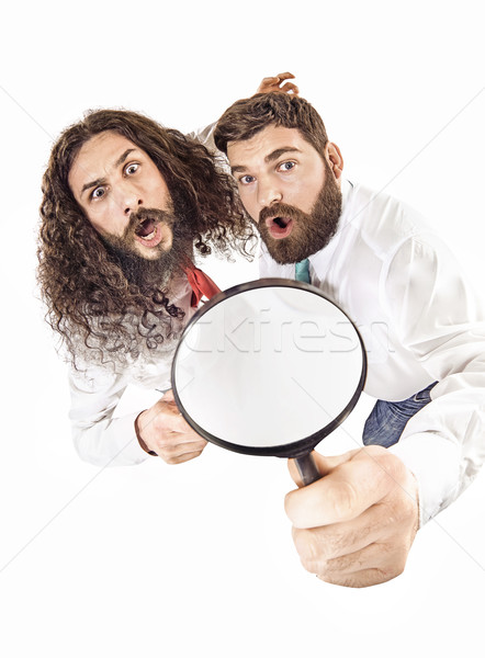 Two colleagues using a magnifying glass Stock photo © konradbak
