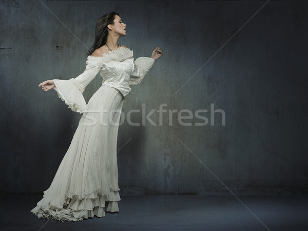 Beautiful woman wearing white dress over a grungy wall Stock photo © konradbak