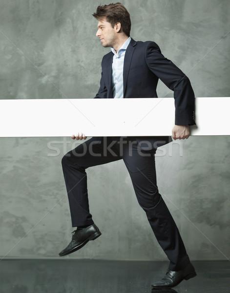 Young man carrying the white board Stock photo © konradbak