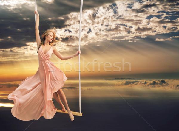 Attractive young lady on a swing above the sea Stock photo © konradbak