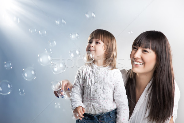 Smiling woman and her daughter Stock photo © konradbak