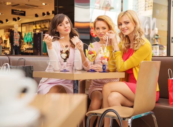 Stock photo: Portrait of the young girlfriends eating ice cream