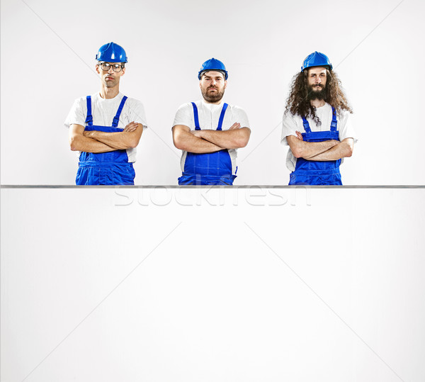 Stock photo: Three talented craftsmen with an empty board