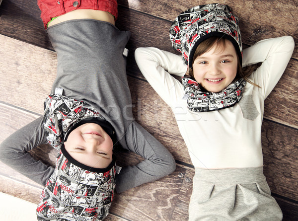 Cheerful siblings lying on the wooden floor Stock photo © konradbak
