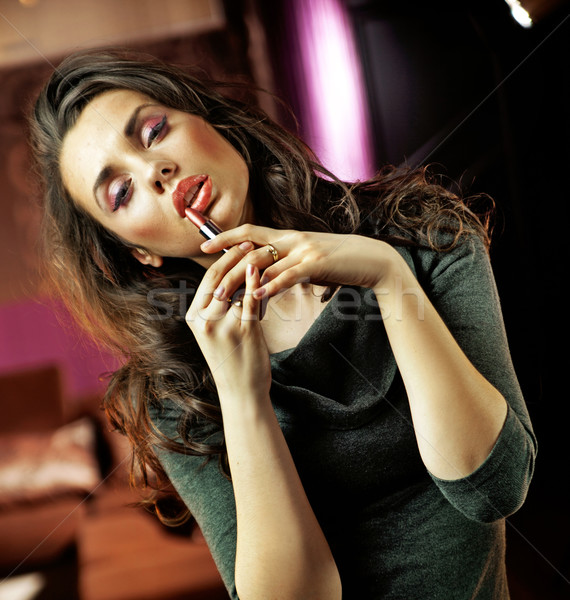Pretty woman holding a lipstick Stock photo © konradbak