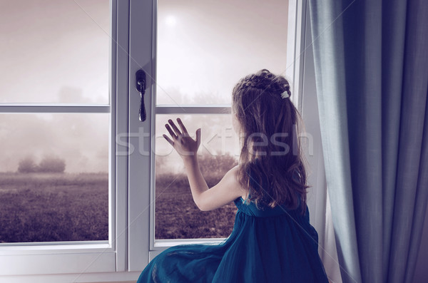 Miserable girl looking through window Stock photo © konradbak