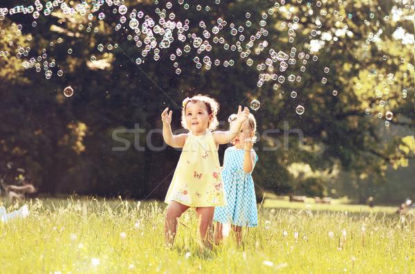 Petite fille bulles de savon été prairie Photo stock © konradbak