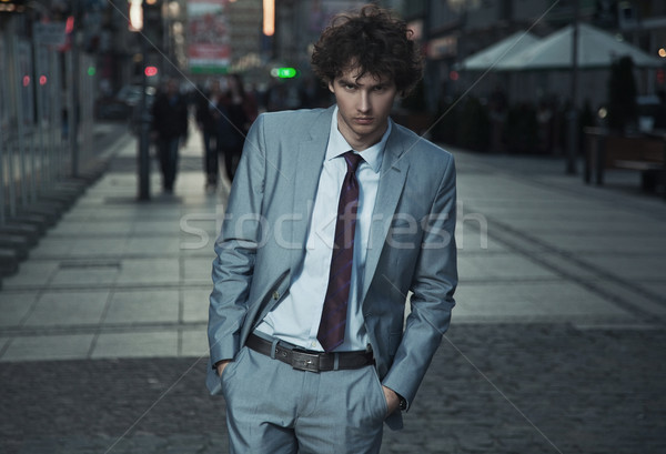 Handsome guy walking on a evening city street Stock photo © konradbak