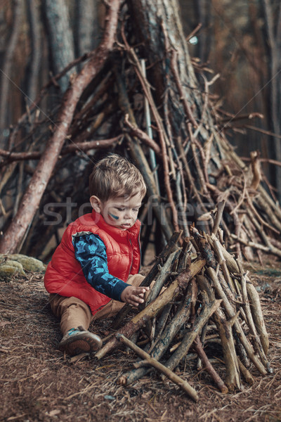 Cute little boy building a wooden shelter Stock photo © konradbak