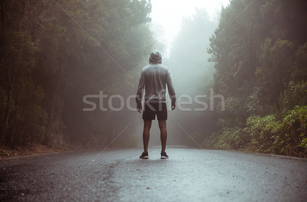 Calm jogger standing on the middle of the road Stock photo © konradbak