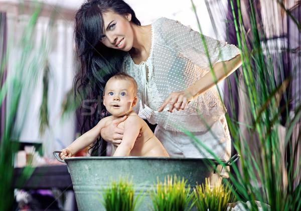 Cute woman cleaning her baby Stock photo © konradbak