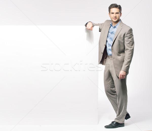 Smart fit guy with large white board Stock photo © konradbak