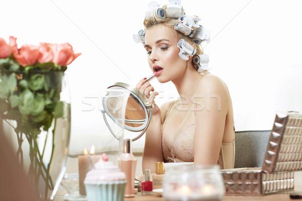 Charming woman putting on a makeup Stock photo © konradbak