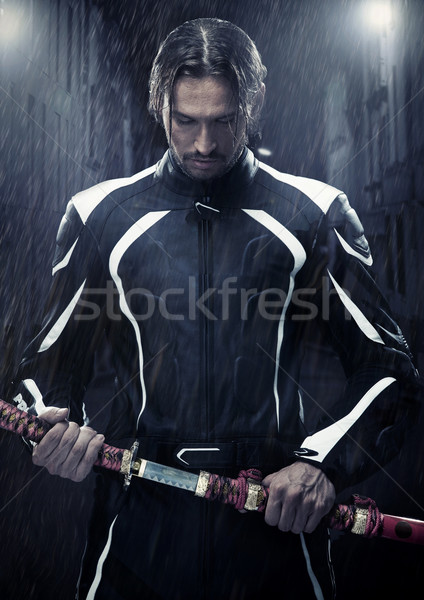 Muscular man holding samurai sword in on a rainy night Stock photo © konradbak