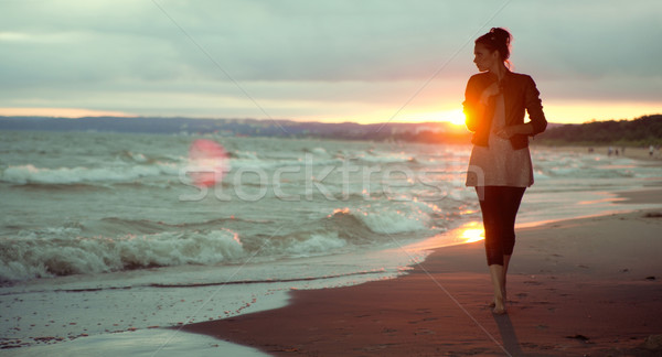 Young woman and the sunset in the background Stock photo © konradbak