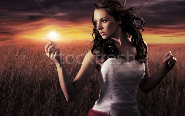 Woman holding a light bulb Stock photo © konradbak
