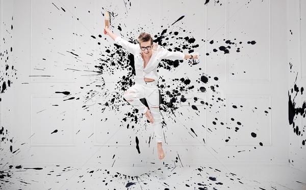 Handsome painter splashing with black paint Stock photo © konradbak