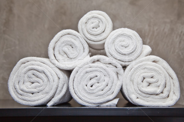 bunch of white towels in bathroom shelf 