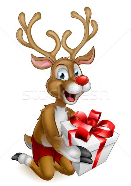 Santas Christmas Reindeer Holding a Gift Stock photo © Krisdog