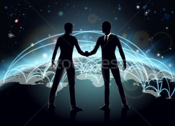 Affaires internationales silhouettes affaires serrer la main carte du monde réseau Photo stock © Krisdog